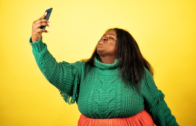 Una bella donna in posa in abiti casual su uno sfondo giallo