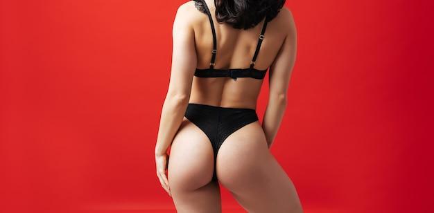 Una bella donna in posa in lingerie su uno sfondo di colore rosso