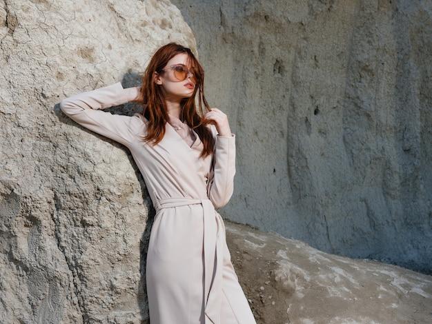 Bella donna che posa vicino alle rocce nella moda di stile di vita della sabbia