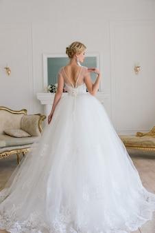 La bella donna in posa in un abito da sposa in interni di lusso