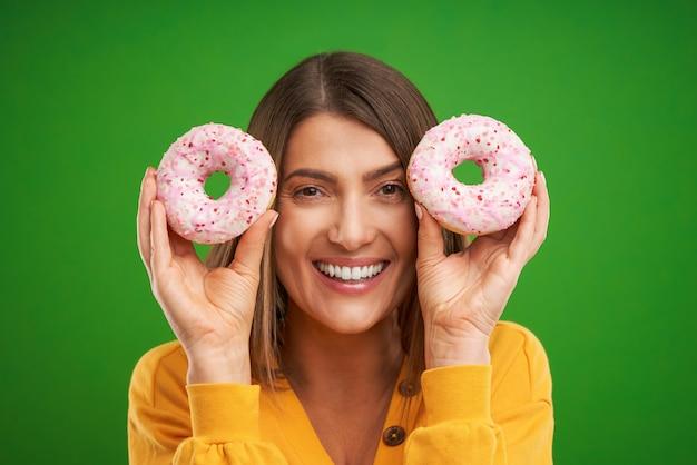 Bella donna in posa con ciambelle su sfondo verde