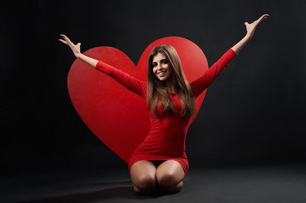 Bella donna che posa con il cuore gigante