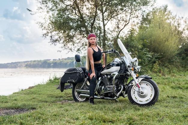 Bella donna in posa con casco e moto