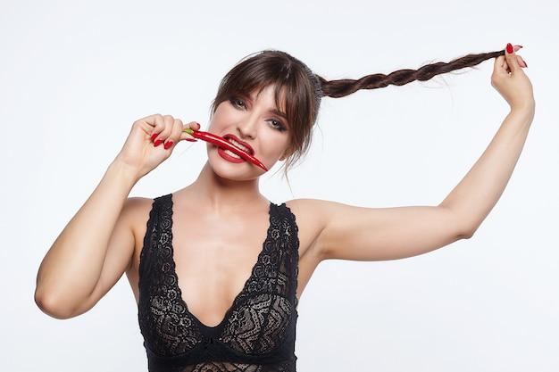 Bella donna che posa con i peperoncini rossi.