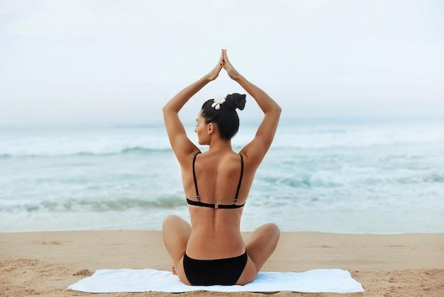 La bella donna pratica lo yoga e medita nella posizione del loto sulla spiaggia. ragazza che fa yoga.