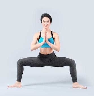 Bella donna a praticare yoga sulla stanza vuota