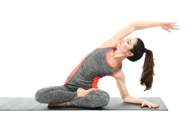 Bella donna che pratica yoga su bianco