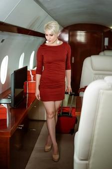 Bella donna in un jet privato in un vestito rosso con una valigia