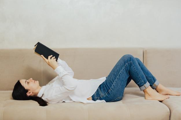 Bella donna che legge un libro e sdraiata sul divano nel soggiorno di casa.