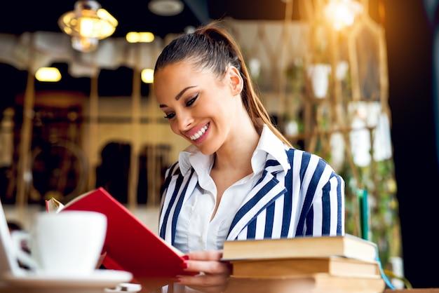 Bella donna che legge un libro alla biblioteca moderna.