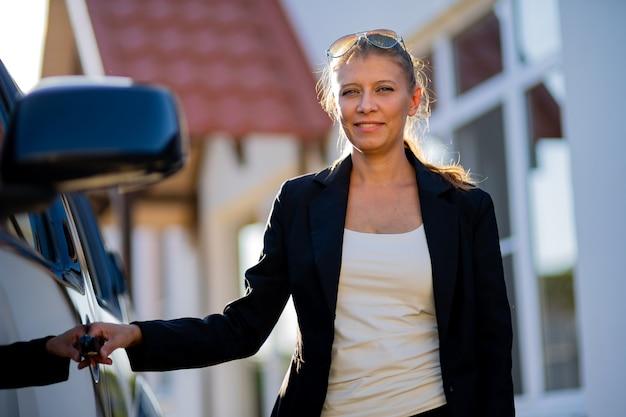 Bella donna agente immobiliare in tuta e auto nera sullo sfondo della casa