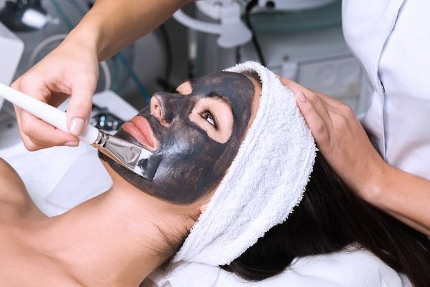 Bella donna che riceve maschera facciale con effetti ringiovanenti nel salone di bellezza spa.