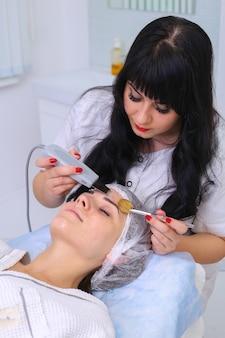 Bella donna che riceve peeling facciale di cavitazione ad ultrasuoni