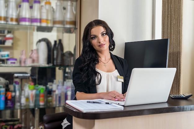 Receptionist della bella donna che sorride al suo posto di lavoro