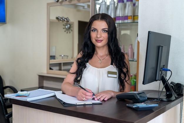 Receptionist bella donna sorridente al suo posto di lavoro
