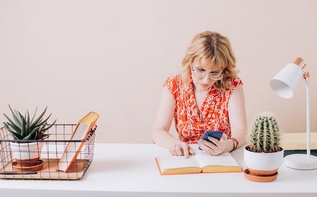 Una bella donna con una camicetta rossa si siede al tavolo e guarda attentamente il telefono e il libro