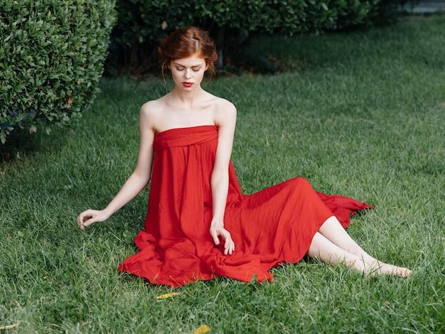 Bella donna vestito rosso glamour natura erba verde lusso. foto di alta qualità