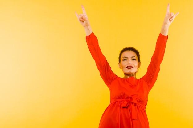 Bella donna in abito rosso in posa mano che fa il gesto delle corna del diavolo su sfondo giallo