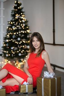 Bella donna in vestito rosso che si siede con le caselle presenti su uno sfondo di albero di natale.
