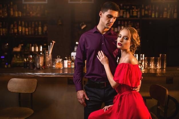 Bella donna in abito rosso con il suo uomo contro il bancone del bar. data in discoteca, coppia di innamorati attraente al pub