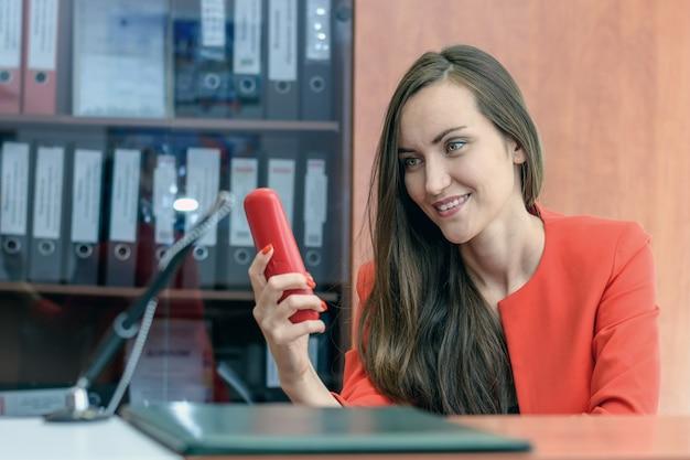 Bella donna in un abito rosso chiamando al telefono. segretario inattivo al lavoro.