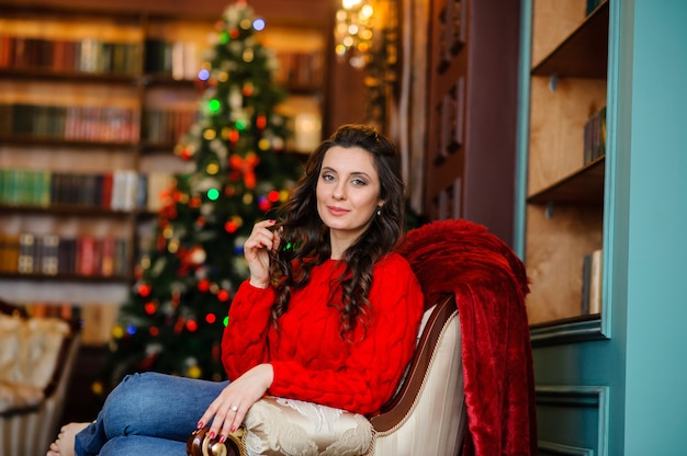 Bella donna in un maglione rosso vicino all'albero di natale