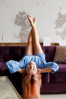 Bella donna che si distende su un divano con la testa sottosopra a casa.
