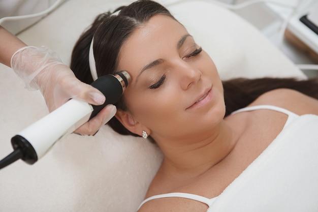 Di una bella donna che si rilassa mentre si fa il viso dal cosmetologo