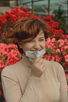 Una bella donna rimuove la maschera protettiva e inspira tra i fiori primaverili. fine del concetto di pandemia di coronavirus