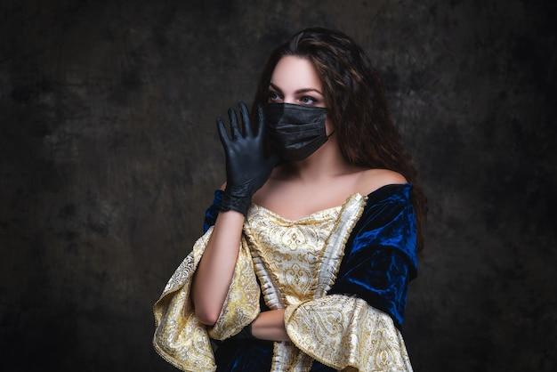 Bella donna in abito rinascimentale, maschera facciale e guanti, coronavirus, concetto di protezione covid-19.