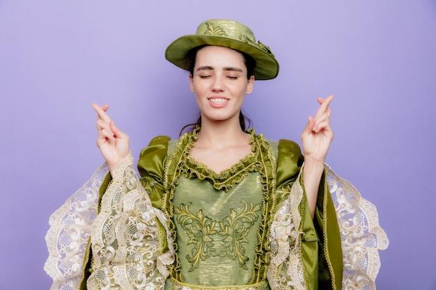 Bella donna in abito rinascimentale e cappello felice e positivo che esprime desideri con espressione di speranza incrociando le dita sul blu