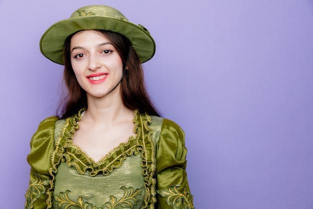 Bella donna in abito rinascimentale e cappello sorridente felice e positivo fiducioso sul blu