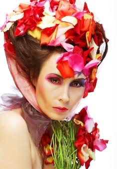 Bello fronte della donna e petali di rosa. trucco da sposa.