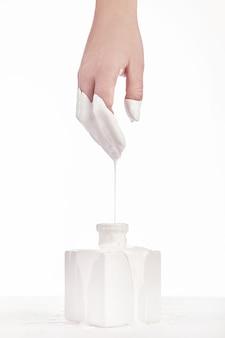 La mano della bella donna, con la sua vernice bianca gocciolante, sfondo bianco. estensione delle unghie. manicure, salone spa. creativo, pubblicitario. rilassare.