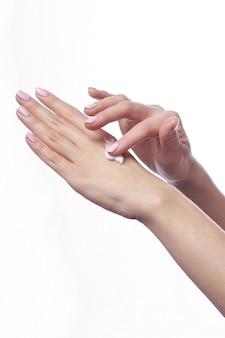 Mani della bella donna con crema cosmetica bianca