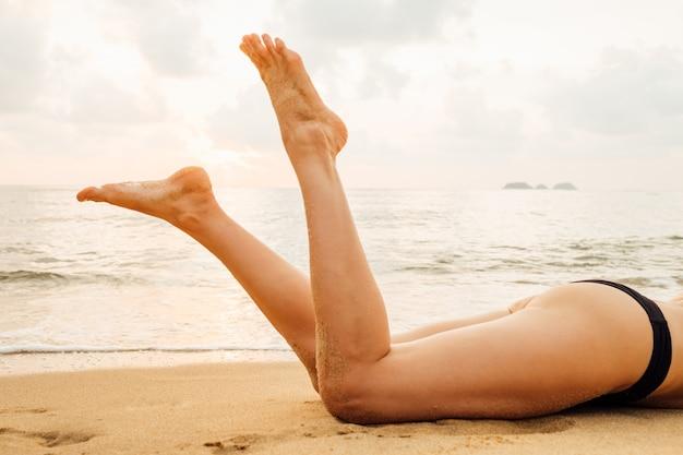 Le gambe della bella donna sulla spiaggia estiva