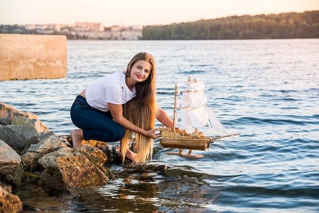 Bella donna che naviga nave giocattolo sull'acqua