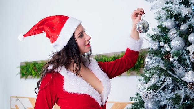La bella donna in un costume sexy di babbo natale decora le decorazioni dell'albero di natale a casa. la ragazza appende una palla d'argento su un albero di natale verde. preparativi per la celebrazione del nuovo anno.