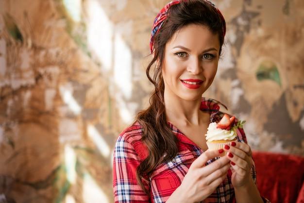 Bella donna in una camicia con il trucco che tiene una torta di fragole, concetto di pin up