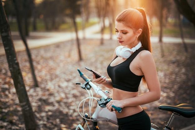 La bella donna in pantaloncini corti e reggiseni legge il messaggio sul telefono vicino alla bicicletta al tramonto nel parco
