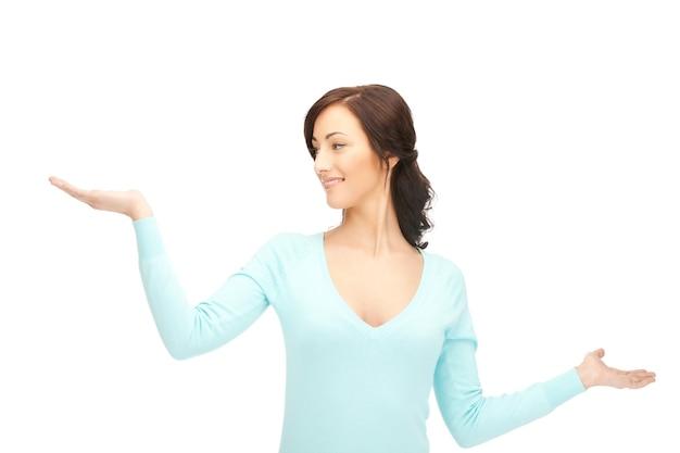Bella donna che mostra qualcosa sui palmi delle mani