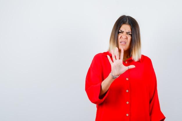Bella donna che mostra il gesto di arresto in camicetta rossa e sembra disgustata. vista frontale.