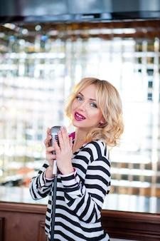 Bella donna canta con un microfono