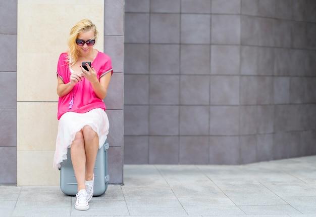 La bella donna si siede sulla valigia guarda il telefono
