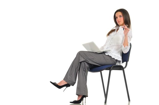 La bella donna si siede sulla sedia con il computer portatile bianco in grembo e una penna in mano. foto su parete chiara