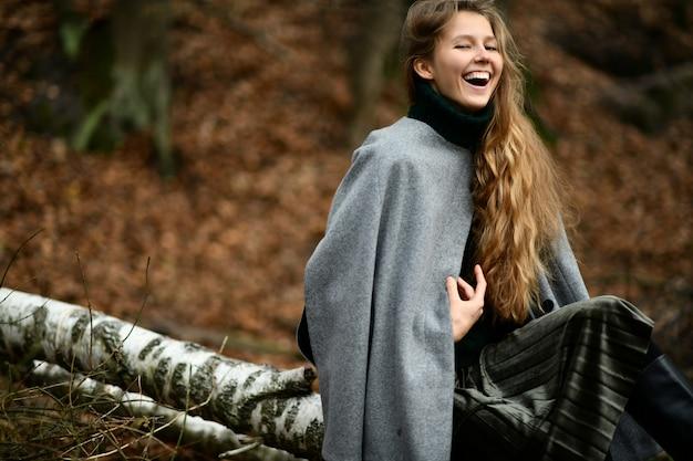 La bella donna si siede nei boschi e ride