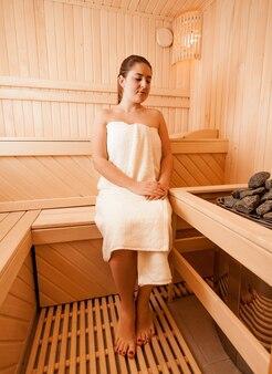 Bella donna seduta su una panchina accanto al forno della sauna