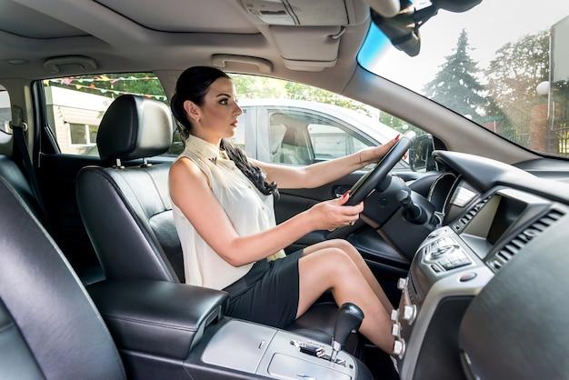 Bella donna seduta nel sedile del conducente all'interno dell'auto