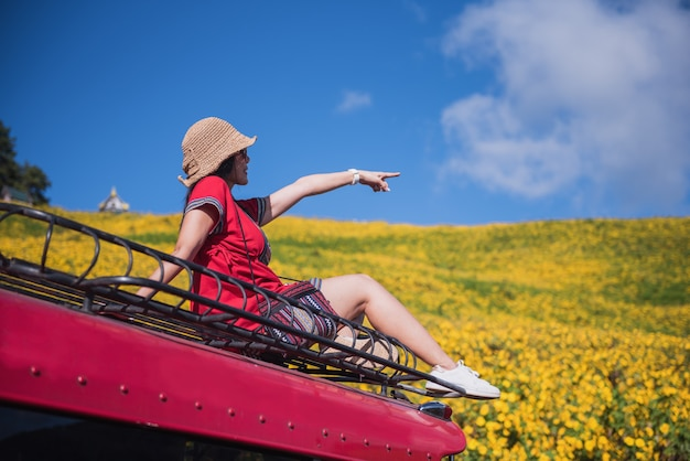 Una bella donna seduta sul tetto di un'auto rossa