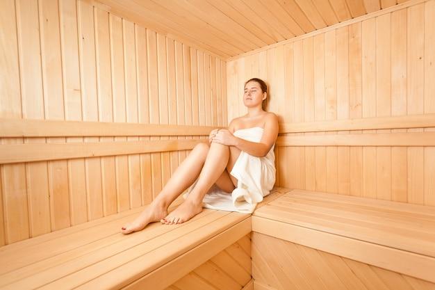 Bella donna seduta nel bagno di vapore in legno wooden